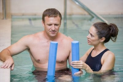 Man in pool with therapist try aquatic therapy for traumatic brain injury