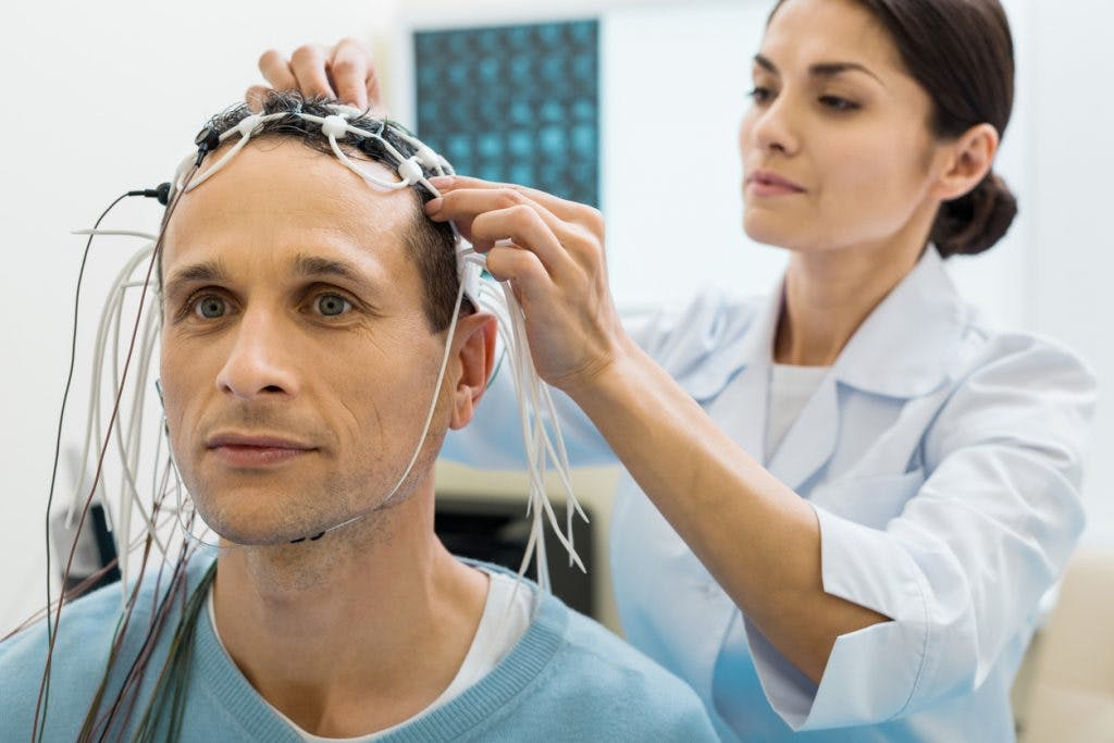 Doctor placing electrodes on man's head during neurofeedback session