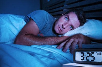 man wide awake at night suffering insomnia, one of the most common TBI sleep disorders