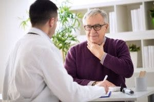 elderly man visiting doctor because of his dysphagia after head injury