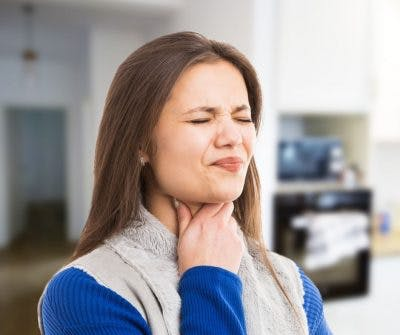 Woman grasping throat and struggling to swallow