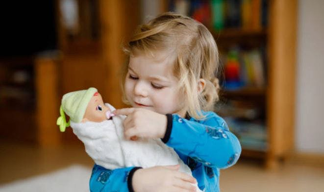 child at play therapy for cerebral palsy with doll