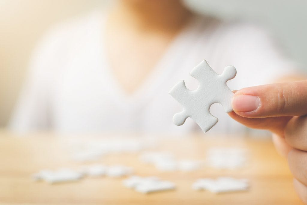 Man holding a puzzle piece, performing a neuropsychological test