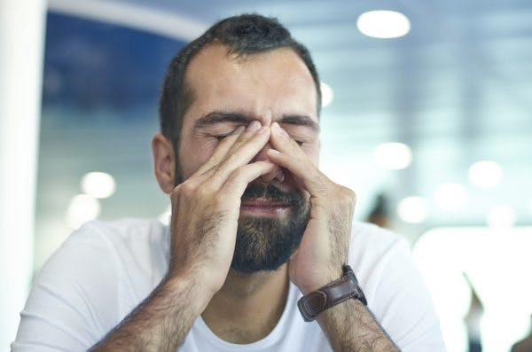 man rubbing eyes, suffering from cognitive fatigue after brain injury sitting on a chair, blur background