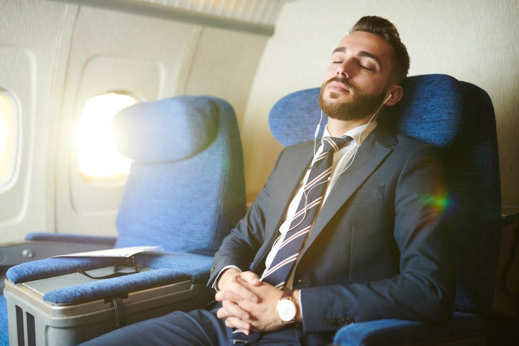 man sleeping on airplane to avoid sensory overload, a danger of flying after brain injury