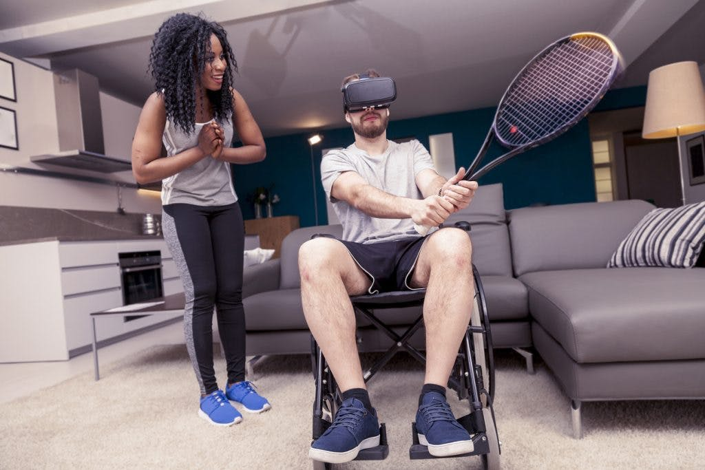 man in wheelchair playing virtual reality tennis as part of his traumatic brain injury rehabilitation