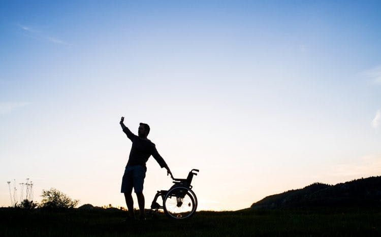 man standing up from wheelchair achieving full recovery from stroke
