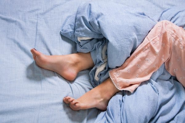 woman with restless leg syndrome fidgeting in bed