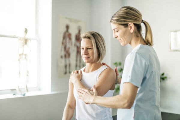Physical therapist teaching patient how to overcome dystonia after brain injury