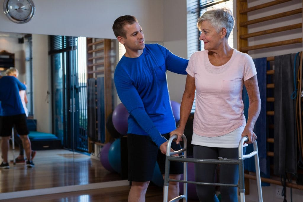 Woman using walker during gait training session with therapist