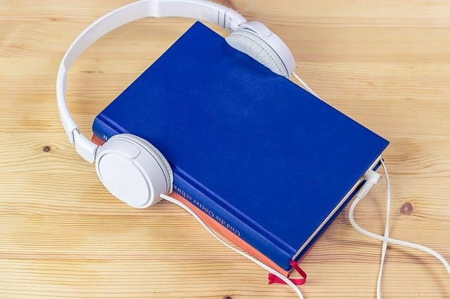 book with headphones symbolizing learning to read again after brain injury