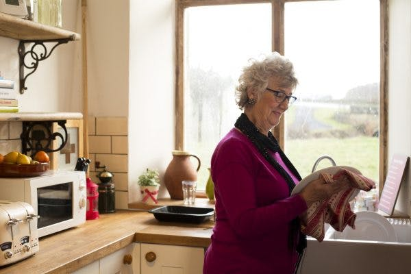 senior woman drying dishes and relearning the activities of daily living after TBI