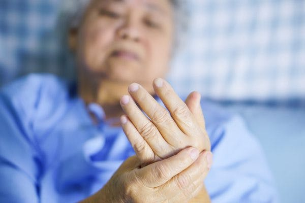 old Asian woman in hospital bed holding shaking hand after stroke