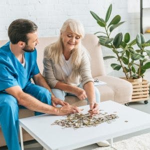 occupational therapist helping smiling senior woman with brain injury finish a jigsaw puzzle