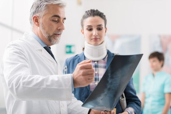 Doctor looking at female patient's x-ray explaining post-traumatic cervical dystonia to her