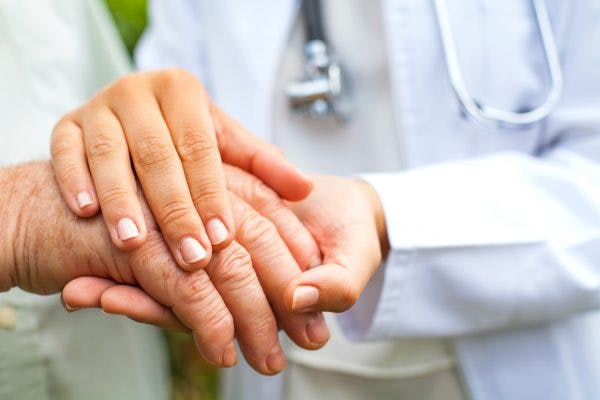 Close up of doctor holding elderly man's trembling hand