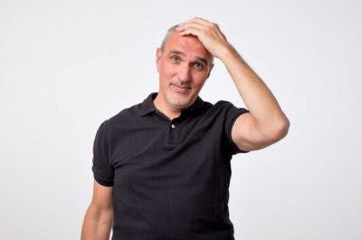 Man with hand on head, looking confused
