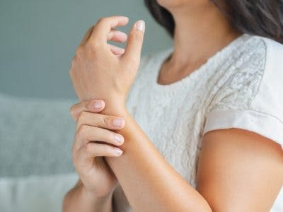 woman holding arm with clonus, a post-traumatic movement disorder