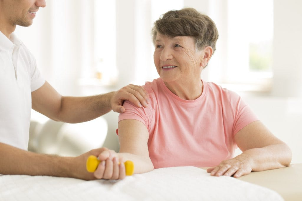 elderly woman exercising with therapist to regain arm movement