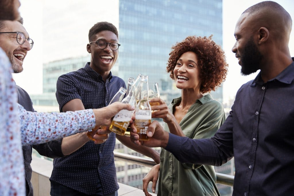 woman smiling with her coworkers, raising glasses to make a toast, using social skills she learned from occupational therapy after brain injury