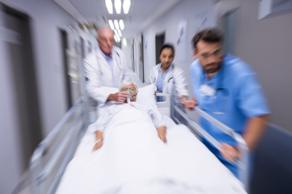doctors rushing to treat a patient with global brain injury