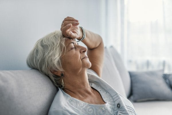 senior woman closing eyes and resting on couch because she suffers from both chronic fatigue syndrome and traumatic brain injury