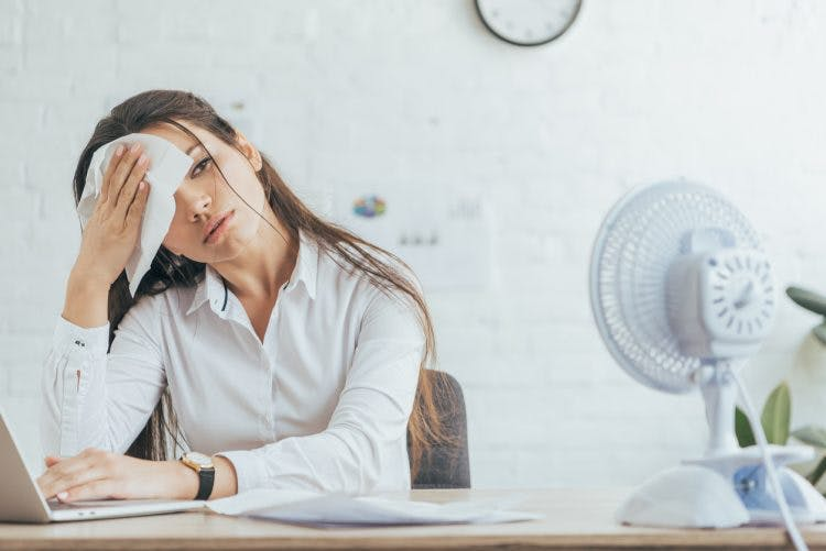 woman wiping head with cloth sitting in front of electric fan in office because she struggles with excessive sweating after brain injury