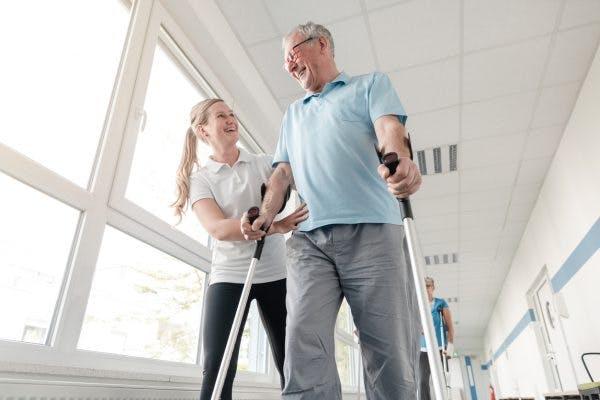 Senior man in TBI rehabilitation learning how to walk again