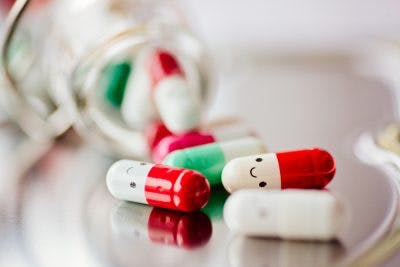Capsule pills with smile on them, representing antidepressants which are medications used for traumatic brain injury