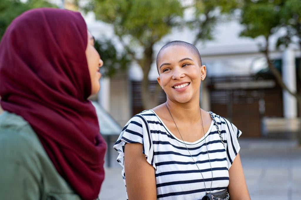 woman smiling and asking advice for a decision from friend