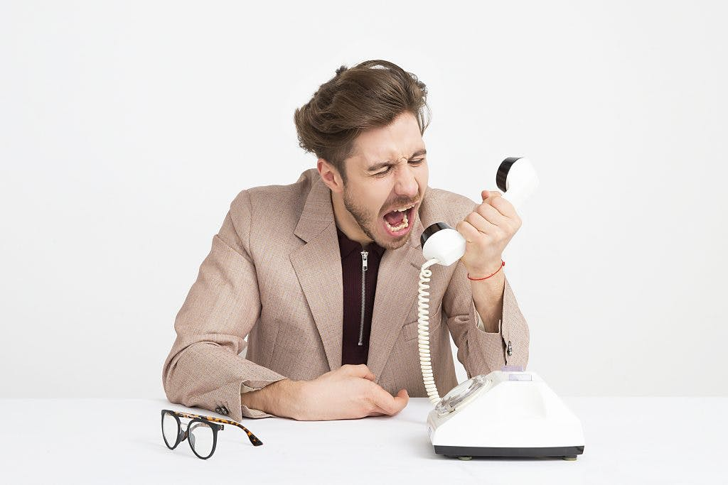 man screaming into telephone because he struggles with aggressive behavior after brain injury