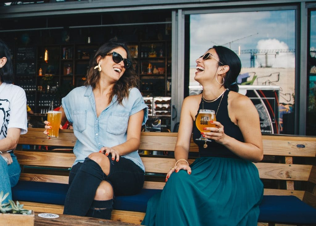two friends laughing and holding drinks and improving their social skills after brain injury