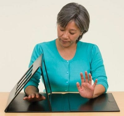 stroke patient using mirror box hand therapy equipment for stroke patients