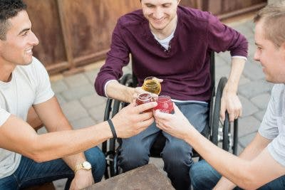 three friends having a drink and enjoying each others company to help their friend overcome lack of motivation after brain injury