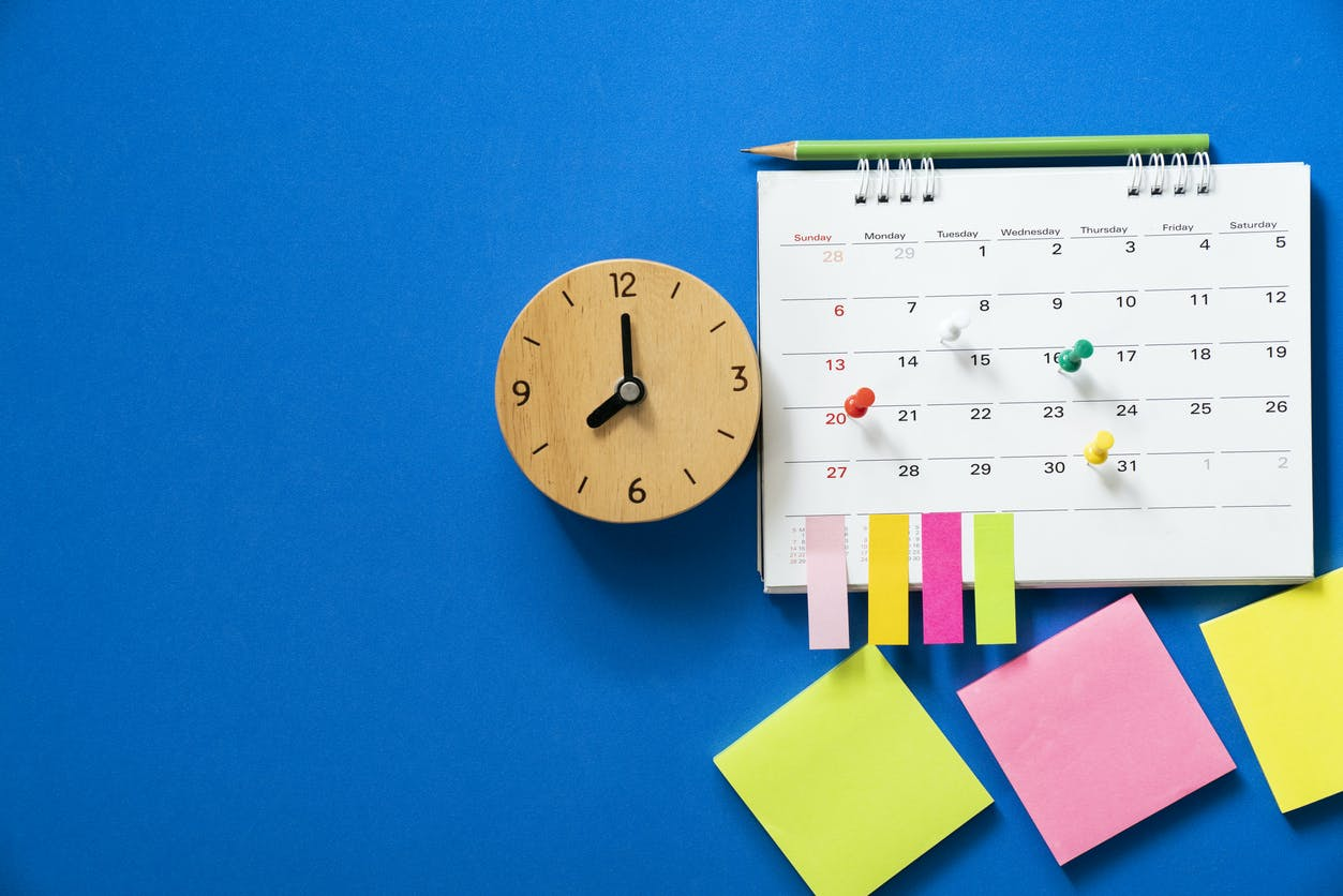 clock, calendar and post-it notes over blue background