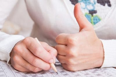 close-up of man giving a thumb's up while doing a word search puzzle, an excellent exercise for left neglect after brain injury
