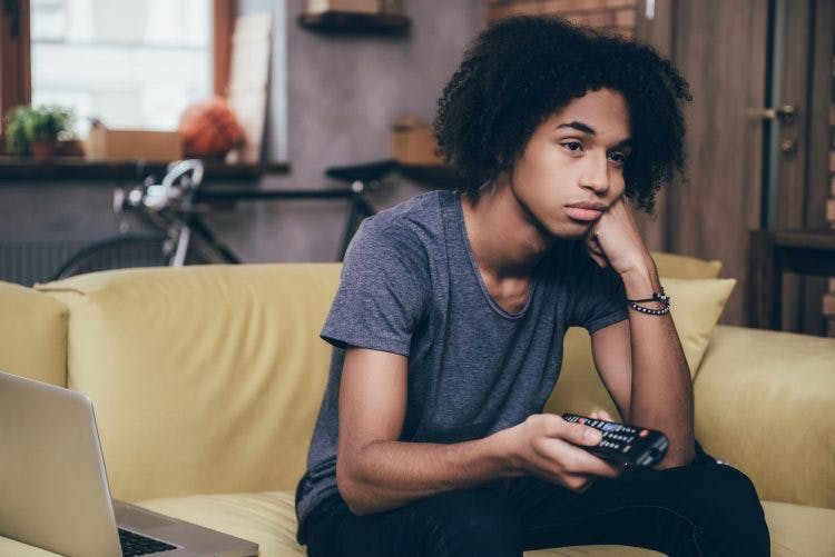 teenager sitting on couch bored and holding remote, struggling with lack of motivation after brain injury