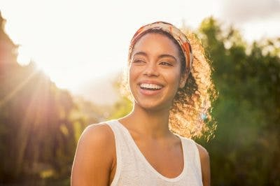 woman smiling and standing in the sunshine to boost her vitamin D, which can help with chronic fatigue syndrome and traumatic brain injury