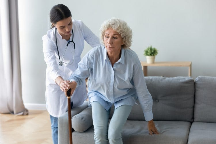 nurse helping elderly patient with basal ganglia brain damage stand up from sofa