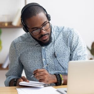 Man wearing headphones and writing in notebook, using brain injury memory strategies to help him remember
