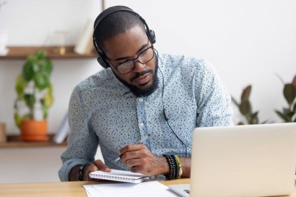 Man wearing headphones and writing in notebook, using brain injury memory strategies to help him remember