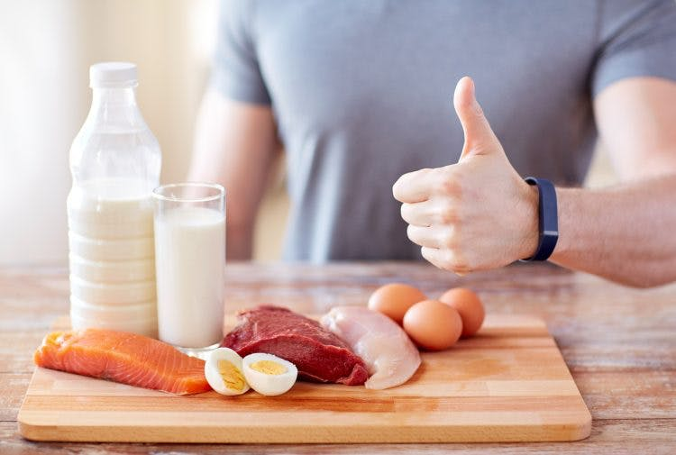 man with food rich in vitamin B12 for brain injury showing thumbs up