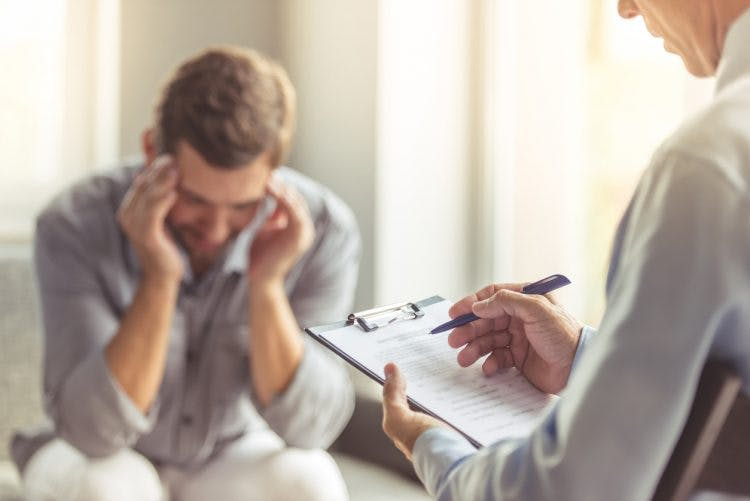 man working with psychologist to overcome symptoms of orbitofrontal cortex damage