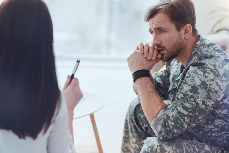 soldier listening to doctor describe blast-induced traumatic brain injury