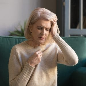 woman sitting on couch closing eyes experiencing nausea and vomiting after head injury
