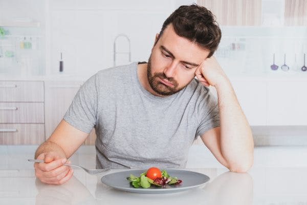 man looking at plate of food not hungry because he is fighting weight loss after brain injury