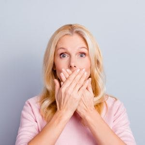 woman covering her mouth to symbolize that she cannot speak because she has aphasia after TBI