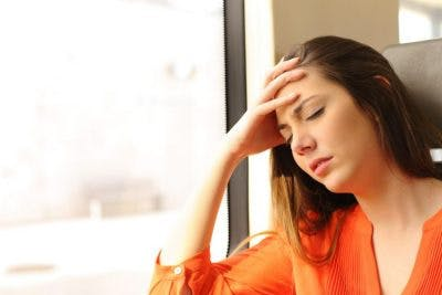 woman sitting by window, closing eyes and looking sick because she is experiencing nausea and vomiting after head injury