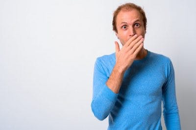 man in blue shirt covering mouth with hand because he has expressive aphasia after tbi