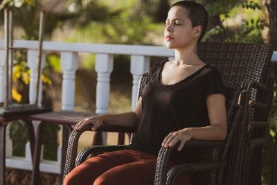 woman closing eyes and sitting in chair on porch, learning mindfulness after brain injury